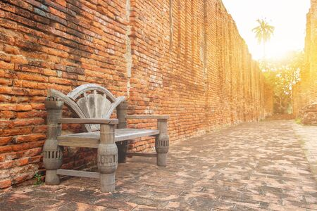Vintage chair wooden and traditional red brick wall exterior wall with sunshine morning. Surface texture masonry bright cleaned brickwork background.