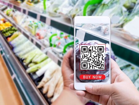 Online order grocery shopping on touch screen concept. Woman hand holding smart phone with checks the QR code or e-wallet on label for ingredient and payment. Business and technology for lifestyle.