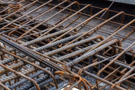 Steel reinforcing tie wire work at construction site of embankment for canal path and protecting riverbank collapse structures. rebar bars reinforcement for reinforced concrete. 免版税图像