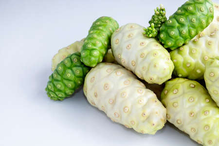 Noni fruit or Morinda Citrifolia noni pile on white table with isolated white background, it is good source of vitamin edible and delicious for healthy.