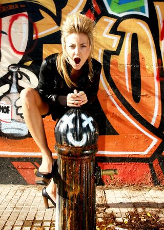 jacked: Screaming blond punk girl in front of a Graffiti wall. with a leader jacked and high heels one feet on a hydrant
