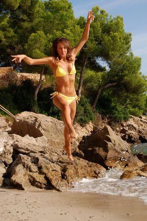 yellow bikini: Sexy ragazza salto in bikini giallo sulla spiaggia di sabbia