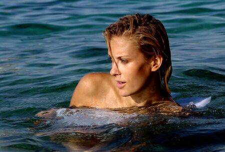 Beautiful blond lady swimming in the sea photo