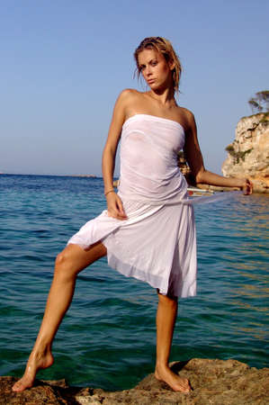 Blond fashion model in sexy pose in the sea on a rock photo