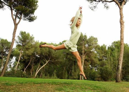 Blond girl jumping on a golf course in a nice green dress photo