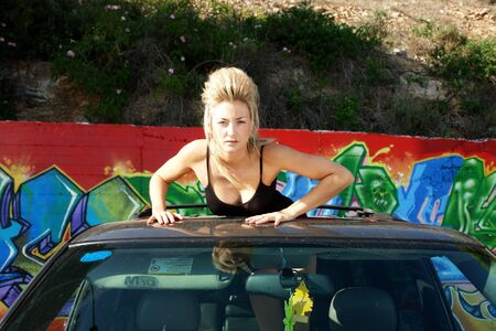 unk girl with looking out of the sun roof of a car photo