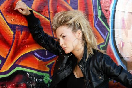 troublemaker: Blond punk girl with a leather jacked in front of grafitti wall Stock Photo
