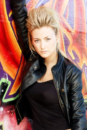 Blond punk girl with a leather jacked in front of grafitti wall Stock Photo - 2601970