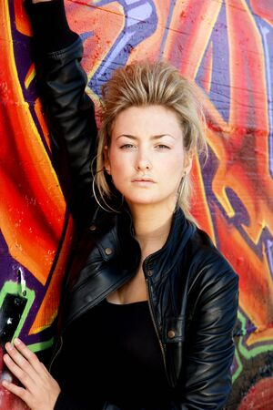 misbehaving: Blond punk girl with a leather jacked in front of grafitti wall Stock Photo