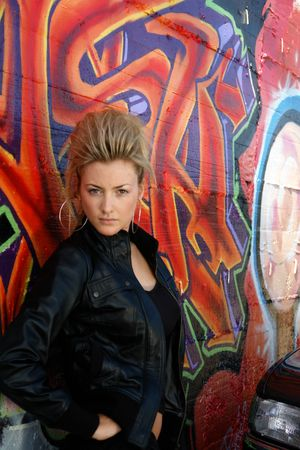supergirl: Blond punk girl with a leather jacked in front of grafitti wall Stock Photo