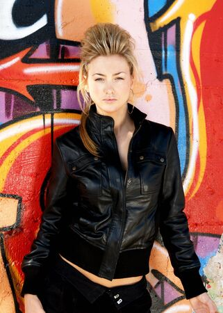 jacked: Blond punk girl with a leather jacked and high heels in front of a grafitti wall Stock Photo