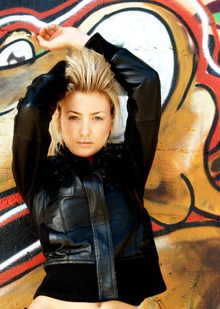 mischievious: Blond punk girl with a leather jacked and high heels in front of a grafitti wall Stock Photo