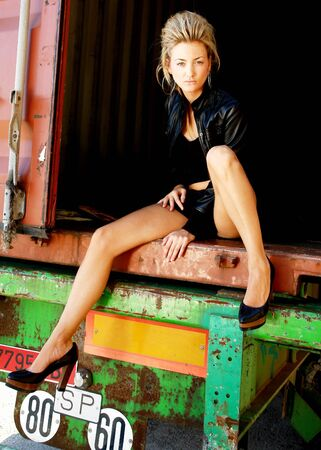 troublemaker: Blond punk girl with a leather jacked and high heels on a back of a lorry Stock Photo
