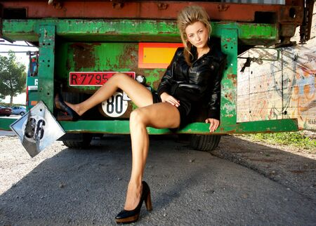Blond punk girl with a leather jacked and high heels standing on a back of a lorry photo