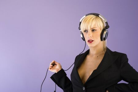 sexy blond girl with deep decolletes with headphones playing with cable photo