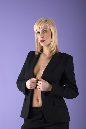 bussiness: serious and sexy blond girl in classic black jacket without bra staying in a strong pose