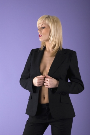 bussiness: serious and sexy blond girl in classic black suit without bra staying in a sensual pose Stock Photo