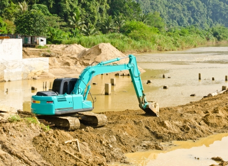 Dredging the canal by a backhoe. Stock Photo