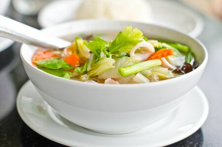 Seafood and vegetable soup in a white bowl. photo