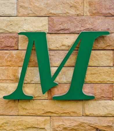 consonant: The letter M on the rock wall