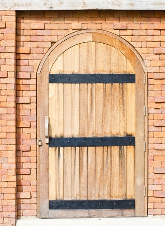 Wooden vintage closed door with brick wall to the house photo