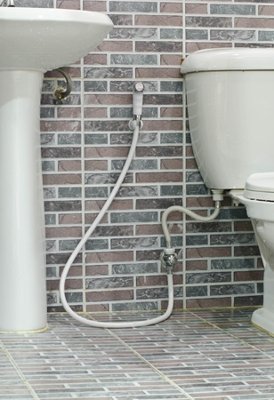 Rinsing Spray or Bidet on the brick wall background photo
