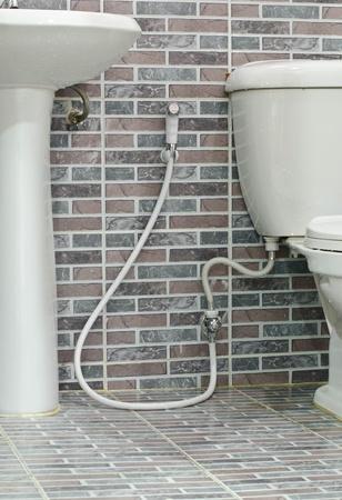 rinsing: Rinsing Spray or Bidet on the brick wall background