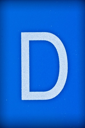 Letter D of the alphabet on blue background  photo