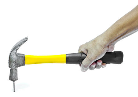 Hammer in hand hitting a nail on a white background
