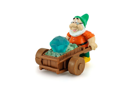dwarfs: Bangkok, Thailand - December 12, 2014: Grumpy character form 7 Dwarfs pushing wheelbarrow with a diamons. There are plastic toy sold as part of the Burger King toys. Editorial