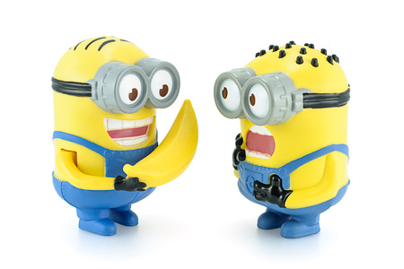 Bangkok,Thailand - February 17, 2014: Minion Dave give banana to Minion figure toy character from Despicable Me 2 movie. There are plastic toy sold as part of the McDonald 報道画像