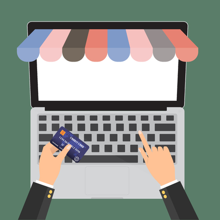 paying: Hand holding credit card for paying in laptop notebook PC with copy space with shop online store. E-Commerce omnichannel online shopping concept.