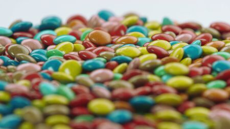Close up of a pile of Colorful coated chocolate Candies Rotating Фото со стока
