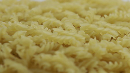 Close up of Uncooked Dry fusilli pasta Rotating