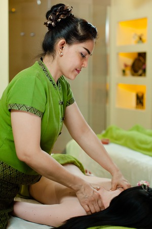 masseur: thay Masseur doing massage on woman body in the spa salon. Beauty treatment concept.