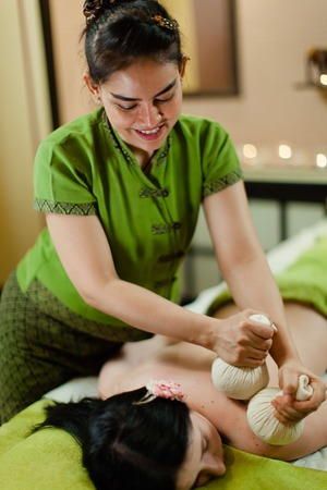 thay Masseur doing Thai herbal hot pack massage on woman body in the spa salon. Beauty treatment concept. Фото со стока