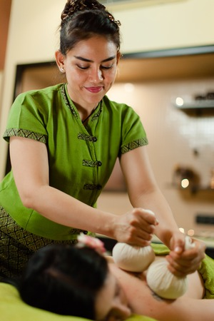 thay Masseur doing Thai herbal hot pack massage on woman body in the spa salon. Beauty treatment concept. 写真素材