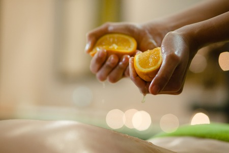 close up of massage with oranges on woman body in the spa salon. Beauty treatment concept.