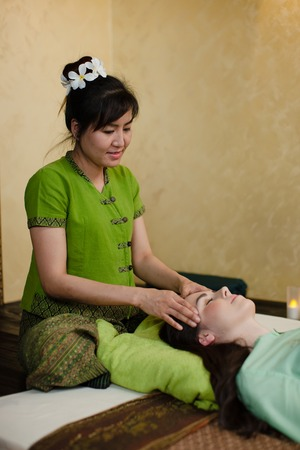 young pretty woman getting thay massage in spa salon