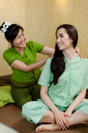 young pretty woman smiling to the Masseur while getting thay massage in spa salon 写真素材