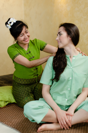 young pretty woman smiling to the Masseur while getting thay massage in spa salon Фото со стока