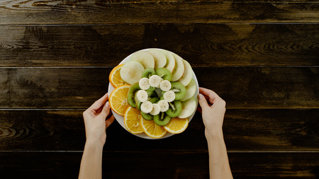 hands holding plate of fruits on the brown wood table top view