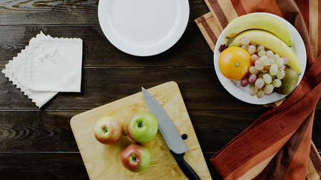 Different fruits lie on plate. Cutting board on the brown table. Фото со стока