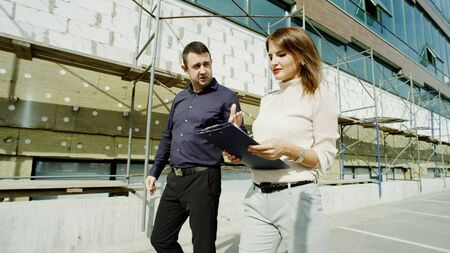 happy businessman and smiling woman in office clothes walking along the building under construction talking and watching at clipboards