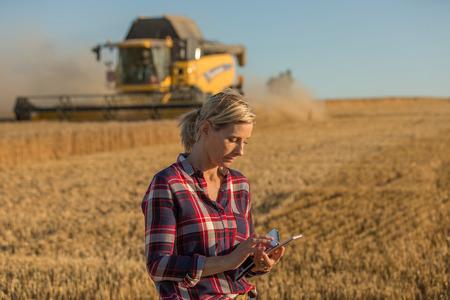 cosechadora: Granjero de sexo femenino y cosechadoras Foto de archivo