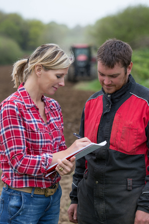 Farmer meeting with agent or advisor for new tractor Insurance Stock Photo
