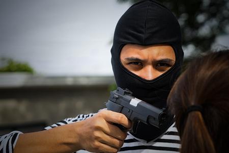 Dangerous Bandit wearing black mask use gun intimidate women in parking In the daytime, Thief Concept.