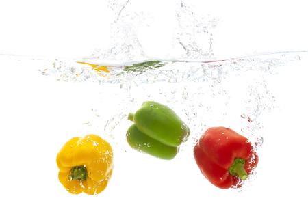 Frescura vegetal pimiento rojo amarillo y verde fruta con salpicaduras de agua fondo blanco espacio de copia para el diseño de su texto.