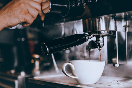 Professionele Barista maker verse koffie met machine in coffeeshop of café.