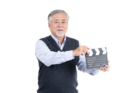 Happy asian elderly man with movie clapper board looking at the camera copy space for your advertisement or promotional text on white background, People lifestyle concept.